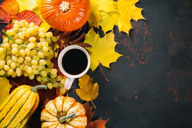 Druiven, merg, pompoenen en koffie met kleurrijke gebladertebladeren.