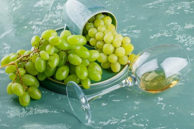 Druiven met drankje in een kopje op gips en lade achtergrond, hoge hoekmening.