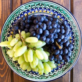 Druiven op een houten achtergrond, wit en zwart.