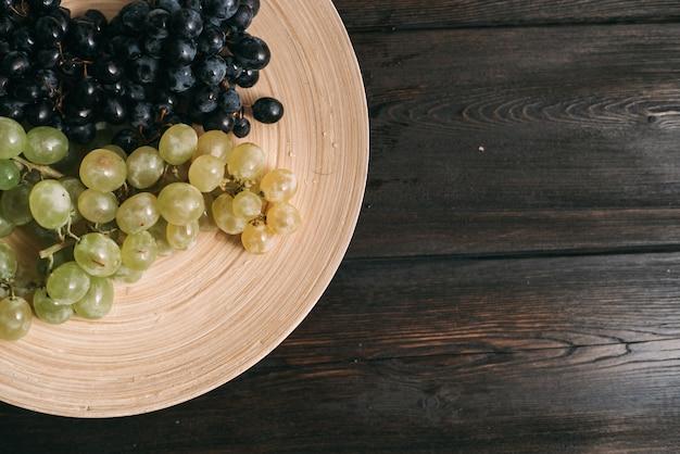 Druiven op een plaat houten fruitversheid.