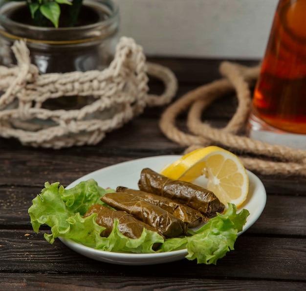 Druivenbladeren dolma gevuld vlees en rijst, gegarneerd met schijfjes citroen