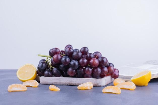Druiventrossen op een houten schotel met rond mandarijnen