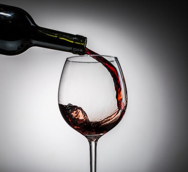 Druivenwijn uit fles in wijnglas van glas wordt gegoten dat