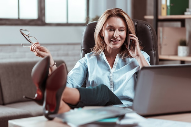 Druk en modern. drukke moderne zakenvrouw die wordt gebeld en e-mail leest op haar zilveren laptop