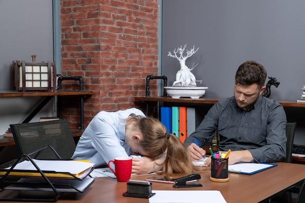 Druk en moe kantoorteam brainstormt over een belangrijk probleem in een kantooromgeving