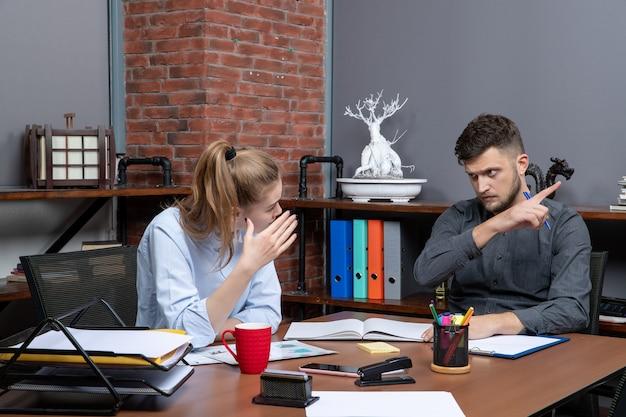 Druk en moe managementteam aan het brainstormen over een belangrijk probleem op kantoor