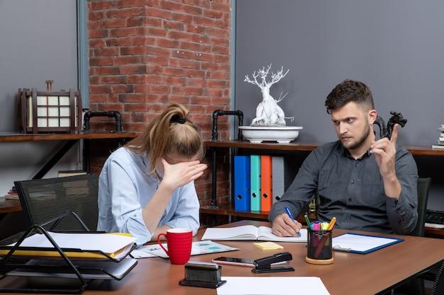 Druk en moe managementteam brainstormt over een belangrijk probleem in een kantooromgeving