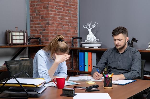 Druk en oververmoeid kantoorteam brainstormt over een belangrijk probleem in een kantooromgeving