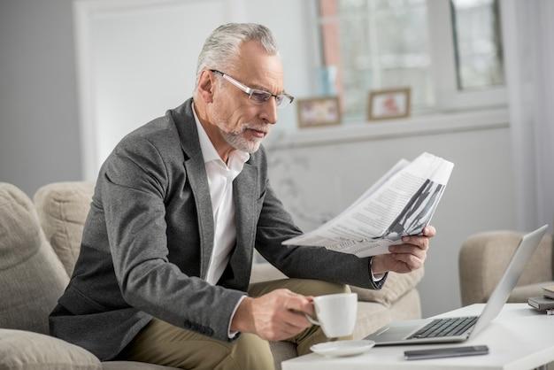 Druk op controle. ernstige gepensioneerde die een bril draagt en een kopje koffie neemt, zittend in halve positie