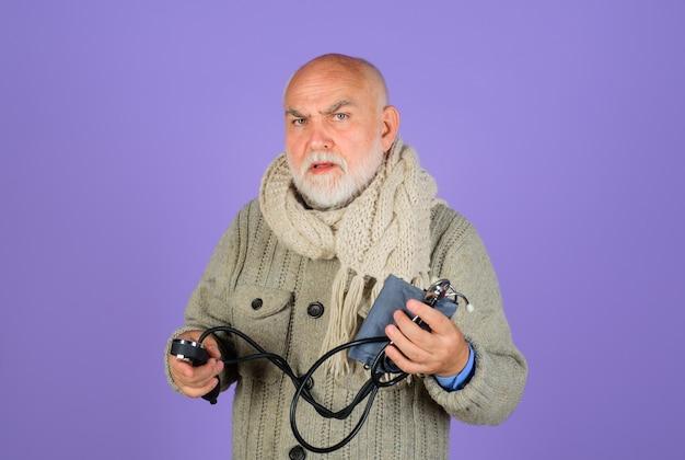 Druk oude man controleren arteriële bloeddruk gezondheidszorg bloeddrukmeter gezondheidszorg concept