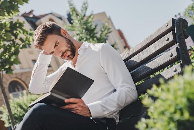 Drukke agenda jonge peinzende man zittend op een bankje in het park kijkend door notities
