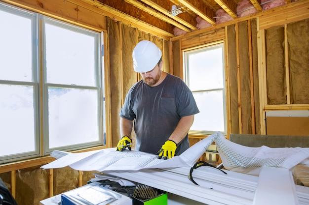 Drukke architect die de details van een blauwdruk controleert die aan een architectuurmodel werkt nieuw project.