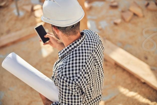 Drukke architect met een rol blauwdrukken en een telefoon