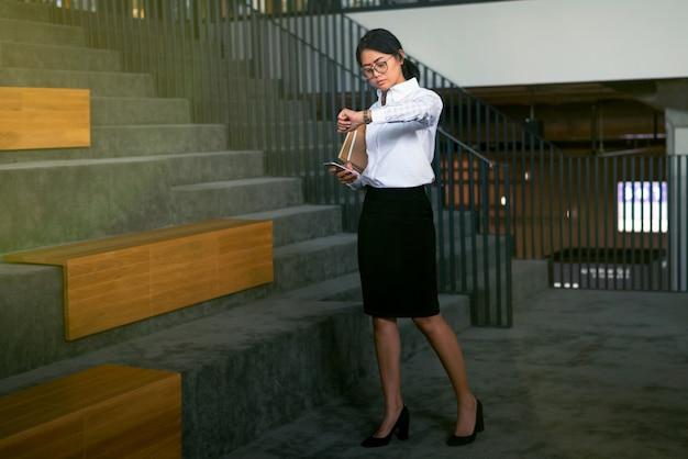 Drukke aziatische zakenvrouw gebruikt smartphone readker-zakenvrouw