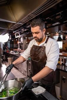 Drukke bebaarde chef-kok in schort staande op fornuis en kokende broccoli in pot op keuken