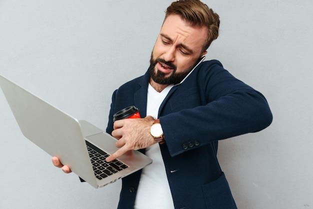 Drukke bebaarde man in zakelijke kleding praten door smartphone