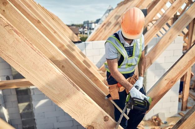 Drukke bouwplaatswerker die beschermende uitrusting draagt en een kettingzaag gebruikt om hout te zagen voor de bouw