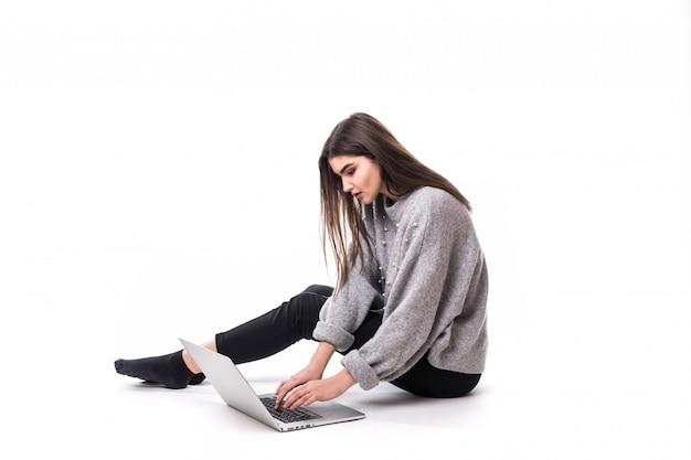 Drukke brunette meisje model in grijze trui zitten op de vloer en studie op haar laptop