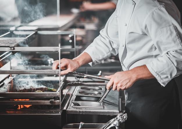 Drukke chef-kok aan het werk in de keuken van het restaurant