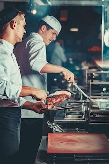 Drukke chef-koks op het werk koken biefstuk in het interieur van de moderne professionele keuken