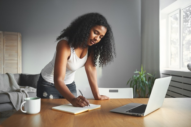 Drukke dag van moderne afrikaanse vrouw die bij houten bureau in gezellige kamer staat, iets opschrijft in haar dagboek, met geconcentreerde gezichtsuitdrukking. mensen, levensstijl en technologieconcept