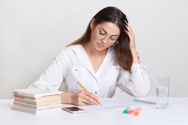 Drukke donkerharige vrouw maakt aantekeningen, onderstreept informatie in kranten, draagt witte blouse, bril, omringd met stapel boeken, smartphone, glas water, geïsoleerd op witte studo muur