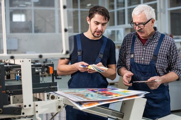 Drukke drukkerijmedewerkers staan bij afgedrukte pagina's en kiezen kleuren voor de volgende druk