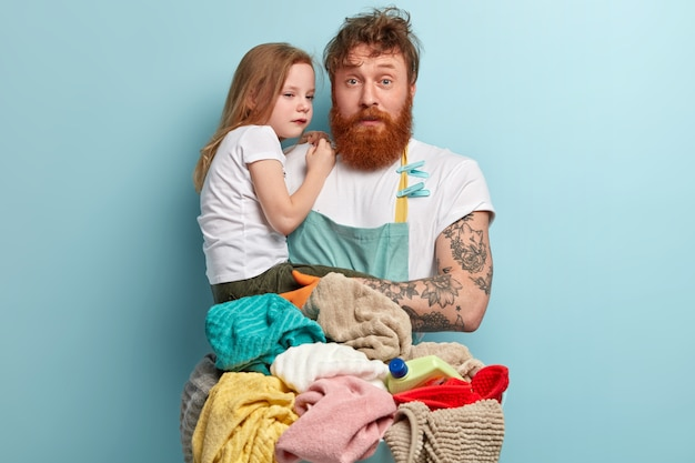 Drukke foxy alleenstaande vader probeert huilend kind te plagen, kijkt verbaasd, draagt een schort, wast wasgoed, heeft veel huishoudelijk werk, geïsoleerd over blauwe muur. vaderschap en bedrijfsconcept