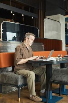 Drukke geconcentreerde volwassen blanke man met snor zittend aan tafel in café en laptop gebruikt tijdens het werken met verzoeken op de website