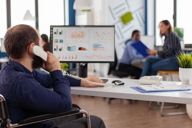 Drukke gehandicapte teamleider die de telefoon beantwoordt en praat met partner die op de computer typt, projectidee uitlegt en financiële gegevens controleert checking