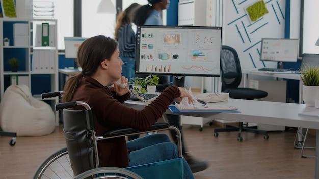 Drukke gehandicapte vrouw die aan de telefoon praat met zakenpartner