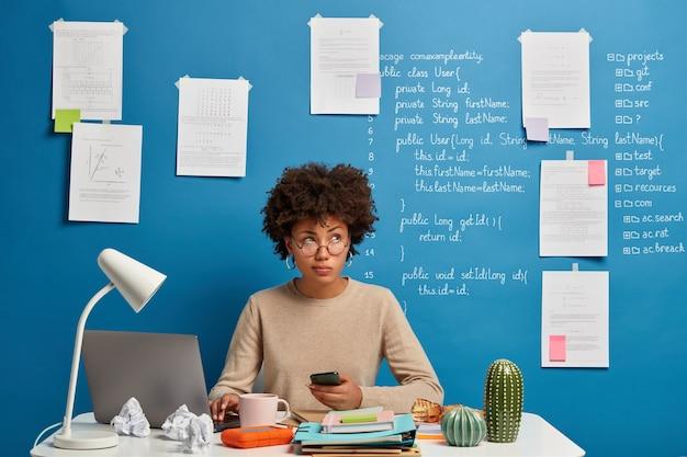 Drukke gekrulde afro-vrouw werkt vanuit huis, gebruikt laptop en smartphone op de werkplek, controleert de nieuwsfeed, vormt op wit bureau met mappen en blocnotes.