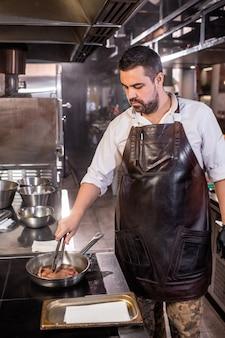 Drukke gezette chef-kok met baard die bij het fornuis staat en een tang gebruikt terwijl hij biefstuk bakt