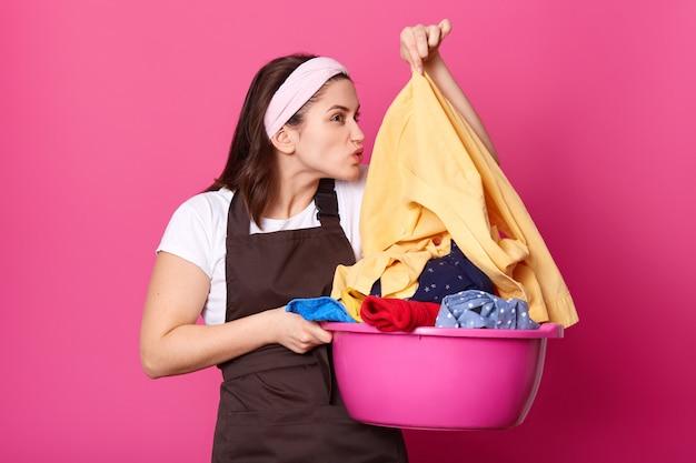 Drukke huisvrouw houdt wasbak van vuile kleren, wast in het weekend, ruikt shirt, gekleed in casual schort en hoofdband, geïsoleerd over roze. huishouden en huis klusjes concept