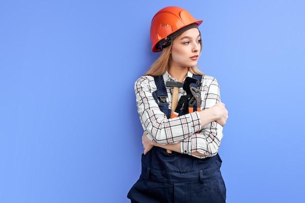 Drukke ingenieur constructor vrouw kijkend naar kant knuffelen verstelbare instrumenten instrumenten geïsoleerd op blauwe studio achtergrond