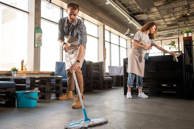Drukke jong koppel in schorten doen schoonmaken in café tijdens de voorbereiding voor opening, kleine bedrijfsconcept