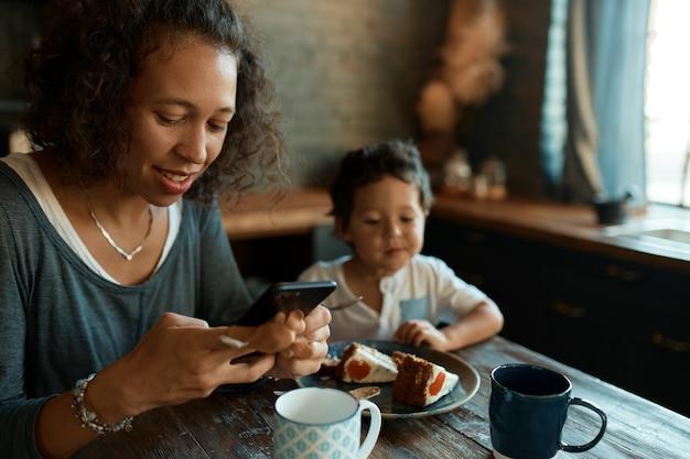 Drukke jonge alleenstaande moeder die mobiele telefoon gebruikt voor werk op afstand, berichten schrijft op sociale netwerkaccounts