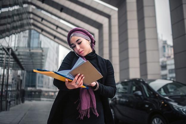 Drukke jonge arabische vrouw staat buiten. ze houdt de gele zak met documenten vast en kijkt naar beneden. modelgesprekken via de telefoon. ze staat dicht bij zwarte auto's.
