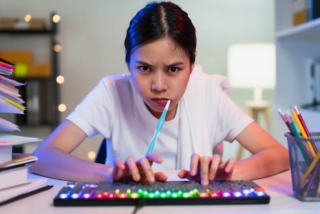 Drukke jonge aziatische vrouw die tanden poetst en met de hand typt op het toetsenbord en haast zich om op tijd te werken