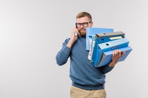 Drukke jonge bebaarde manager met stapel mappen smartphone op het gehoor te houden tijdens het raadplegen van de klant tijdens het werk
