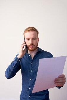 Drukke jonge blanke manager in casual shirt die document analyseert terwijl hij een telefoongesprek voert