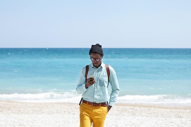 Drukke jonge donkere europese man met modieuze trendy kleding en rugzak die zelfs tijdens vakanties online blijft, een mobiele telefoon op het strand gebruikt en alle schoonheden om hem heen negeert