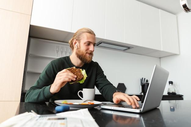 Drukke jonge man aan het werk op laptopcomputer thuis, zittend in de keuken, het drinken van thee