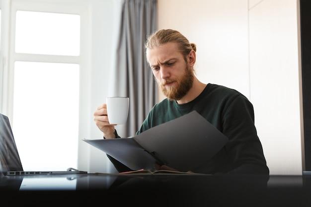 Drukke jonge man aan het werk op laptopcomputer thuis, zittend in de keuken