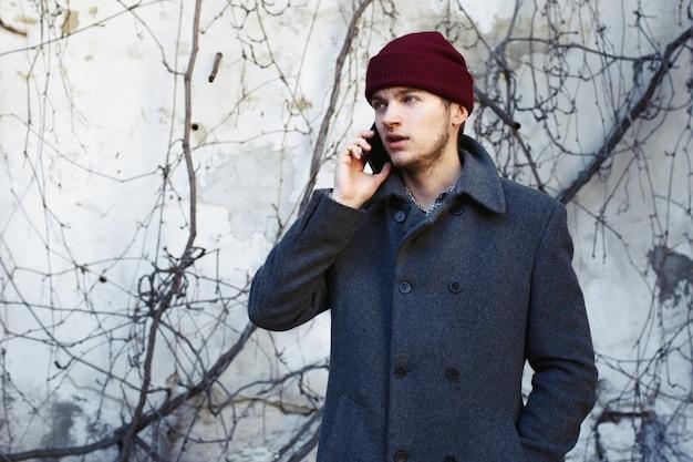 Drukke jonge man in rode hoed praat over de telefoon
