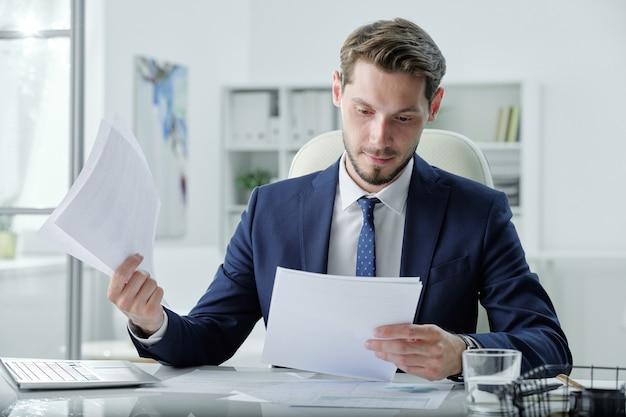 Drukke jonge manager in formele pak zit aan bureau en behandeling van handelspapieren in kantoor