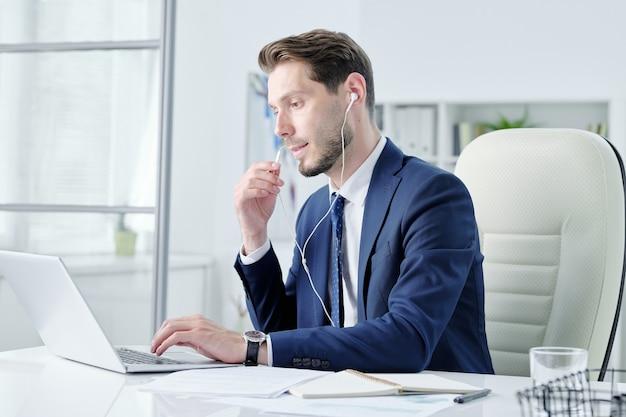 Drukke jonge manager met stoppels aan bureau zitten en praten via oortelefoon tijdens het beantwoorden van vraag aan cliënt met behulp van laptop