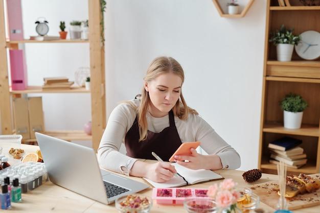 Drukke jonge vrouw met smartphone zittend door werkplek laptop en scrollen door nieuwe bestellingen van klanten