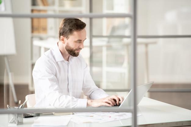 Drukke jonge werknemer in wit overhemd typen op laptop toetsenbord tijdens het kijken naar display tijdens het werk op kantoor