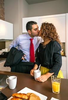 Drukke jonge zakenman zoenen aan gekrulde vrouw die snel ontbijt heeft voordat hij naar zijn werk gaat
